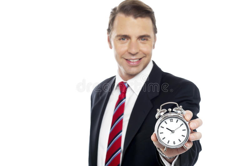 Pokazywać budzika uśmiechnięty młody konsultant zdjęcia stock
