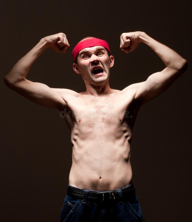 Pokazywać jego bicepsy śmieszny głupek zdjęcie stock