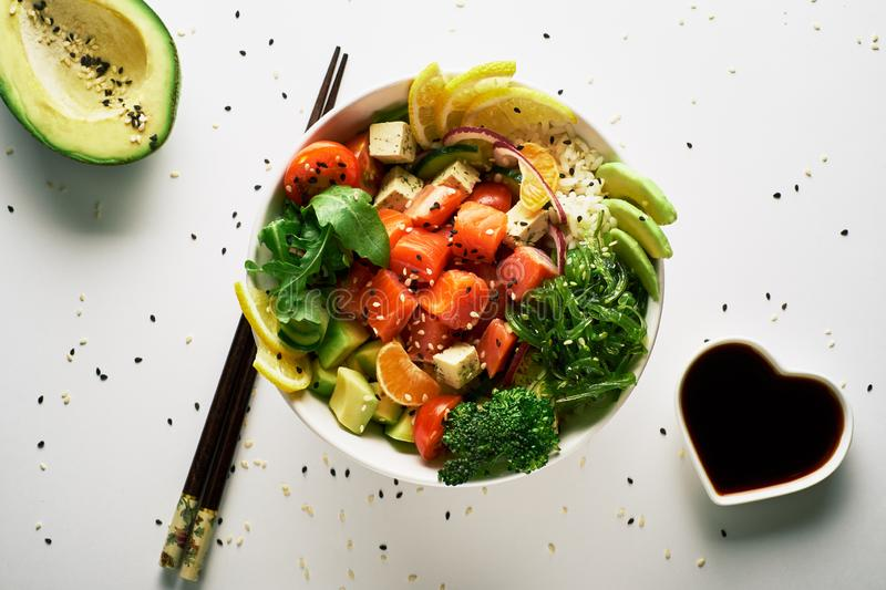poke bowl with salmon, avocado, cucumber, arugula, broccoli, rice, carrot and sweet onions with chuka salad, with chopsticks, stock photo