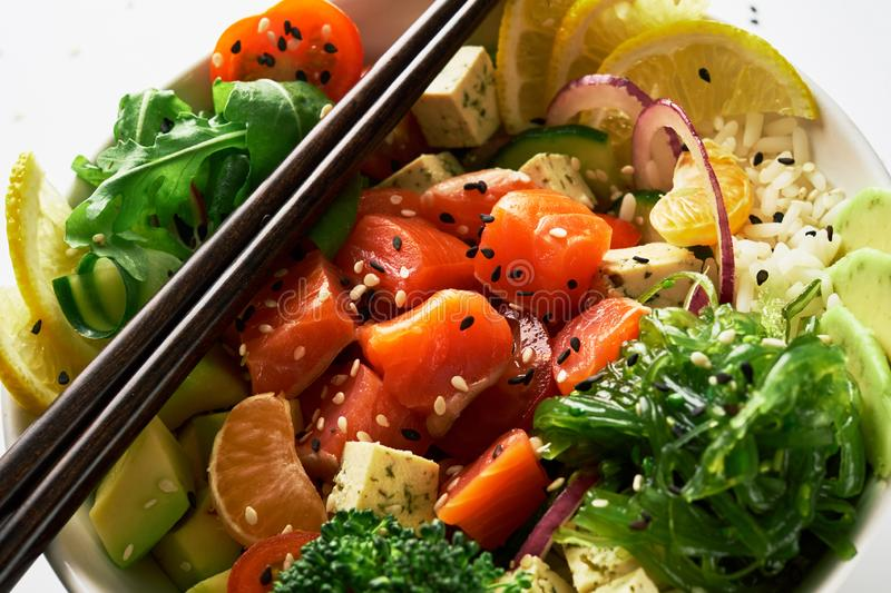 poke bowl with salmon, avocado, cucumber, arugula, broccoli, rice, carrot and sweet onions with chuka salad, chopsticks royalty free stock photo