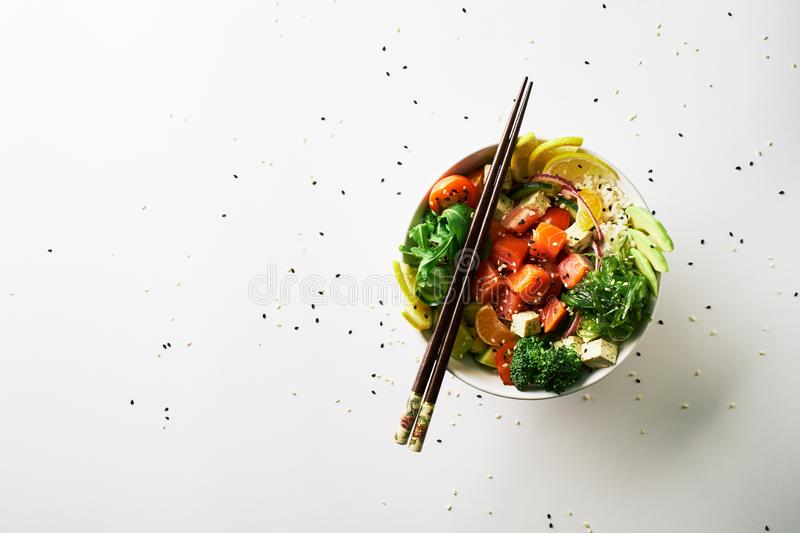 poke bowl with salmon, avocado, cucumber, arugula, broccoli, rice, carrot and sweet onions with chuka salad, chopsticks stock image