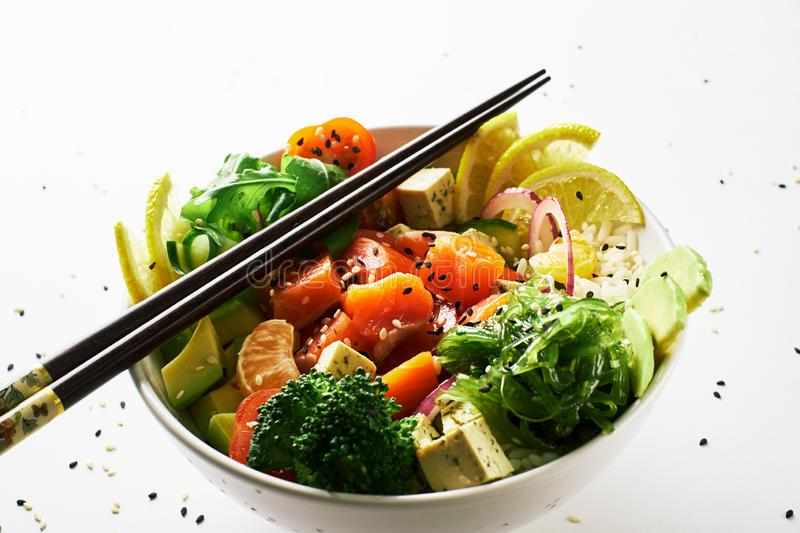 poke bowl with salmon, avocado, cucumber, arugula, broccoli, rice, carrot and sweet onions with chuka salad, chopsticks stock photos