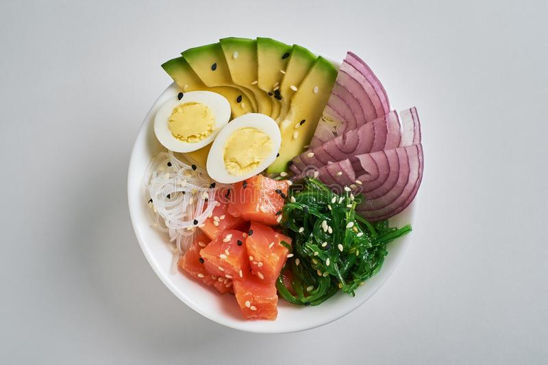 poke bowl with salmon, avocado, rice, Chuka Salad, sweet onions, quail eggs sprinkled with white and black sesame isolated on royalty free stock photo