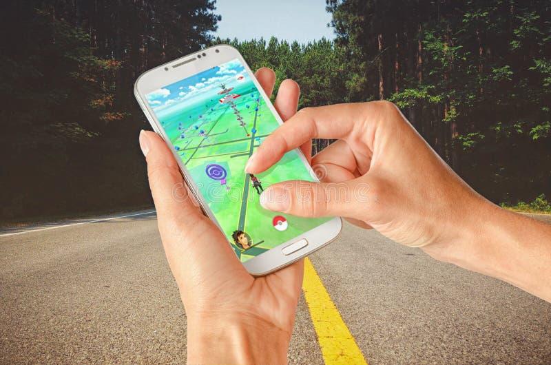 Pokemon在手扶的白色智能手机去 图库摄影