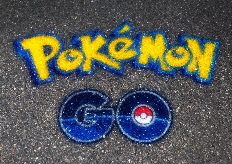 Pokemon шариком логотипа ИДЕТ нарисованным на асфальте стоковые изображения rf