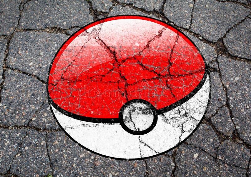 Pokemon шариком логотипа ИДЕТ нарисованным на асфальте стоковые фотографии rf