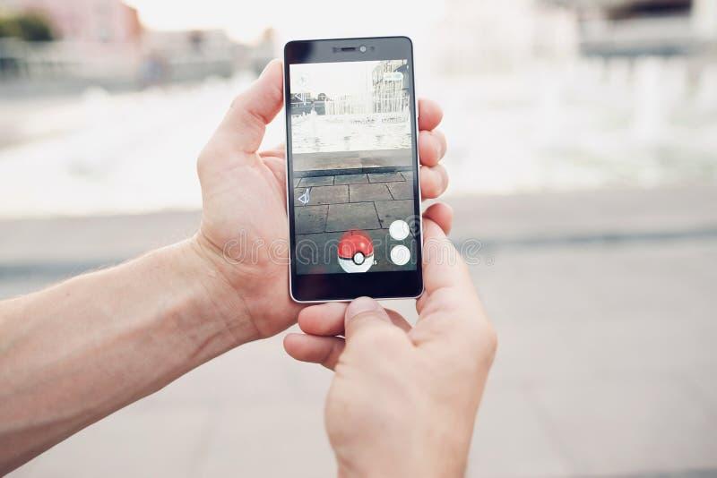 Pokemon Go играя игру smartphone addi стоковое изображение rf