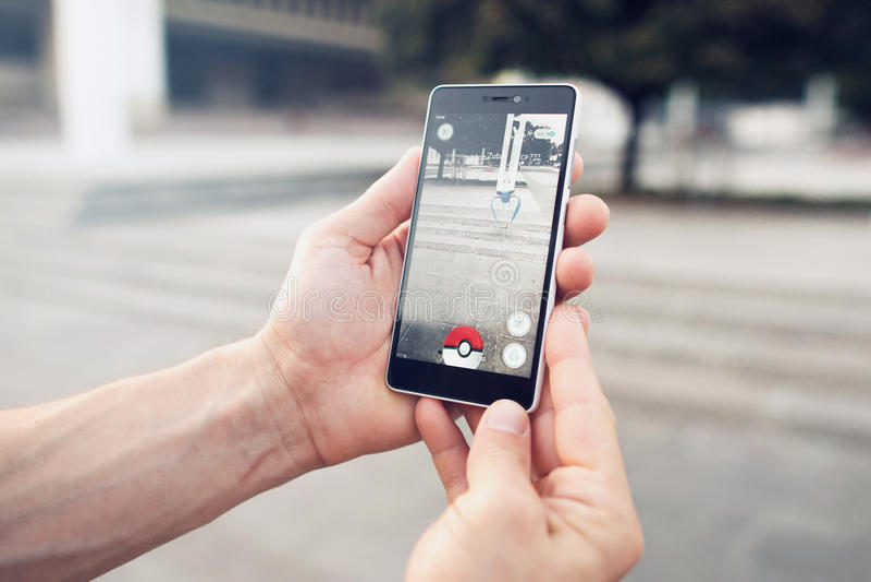 Pokemon Go играя игру smartphone addi стоковое фото rf