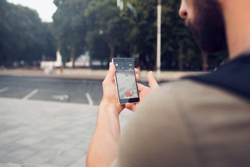 Pokemon Go играя игру smartphone addi стоковое фото