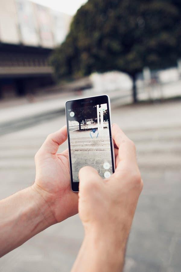 Pokemon Go играя игру smartphone addi стоковые фотографии rf