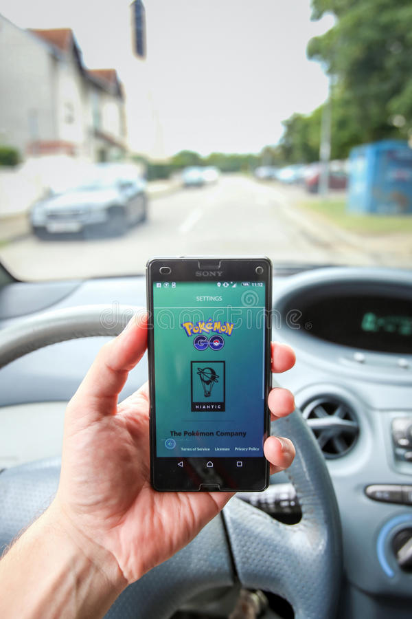 Pokemon Go App. VELIKA GORICA, CROATIA- JULY 15, 2016 : A gamer using a smartphone to play Pokemon Go while driving a car. Pokemon Go is a free-to-play augmented stock photo