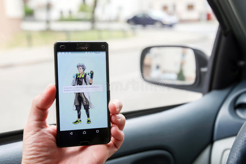 Pokemon Go App. VELIKA GORICA, CROATIA- JULY 15, 2016 : A gamer using a smartphone to play Pokemon Go while driving a car. Pokemon Go is a free-to-play augmented royalty free stock images