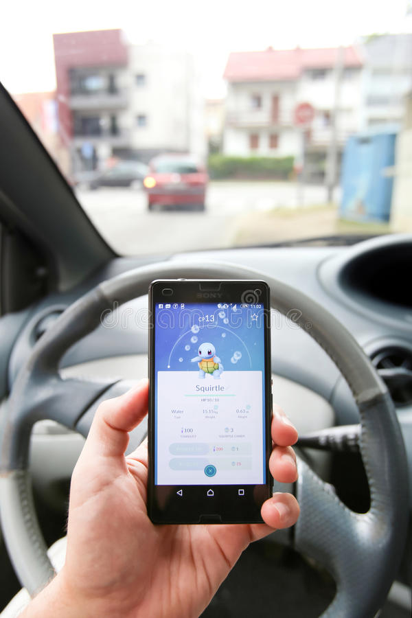 Pokemon Go App. VELIKA GORICA, CROATIA- JULY 15, 2016 : A gamer using a smartphone to play Pokemon Go while driving a car. Pokemon Go is a free-to-play augmented royalty free stock photos
