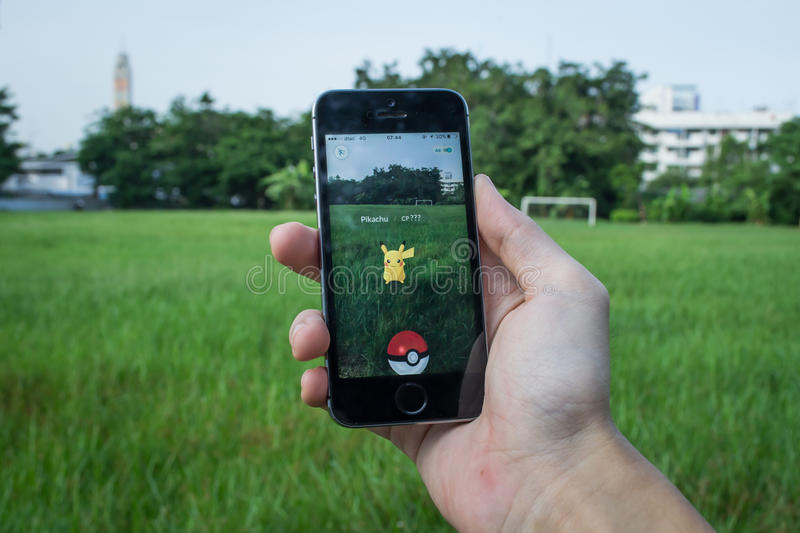 Pokemon Go. Bangkok, Thailand - July 12, 2016 : Apple iPhone5s held in one hand showing its screen with Pokemon Go application royalty free stock photos