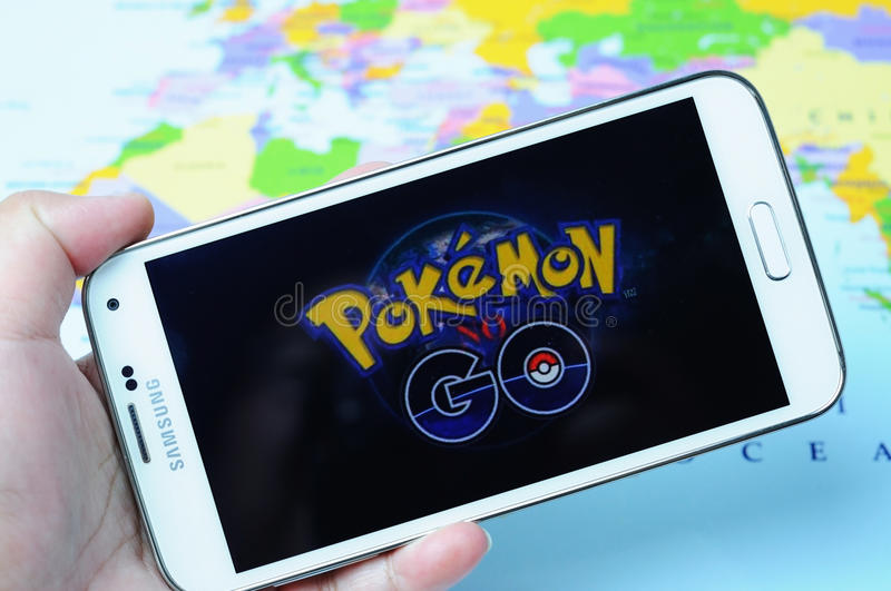 Pokemon Go Logo. KOTA KINABALU, MALAYSIA - 16 JULY 2016: Hands holding a smart phone with screen Pokemon Go logo, a free-to-play augmented reality mobile game royalty free stock images