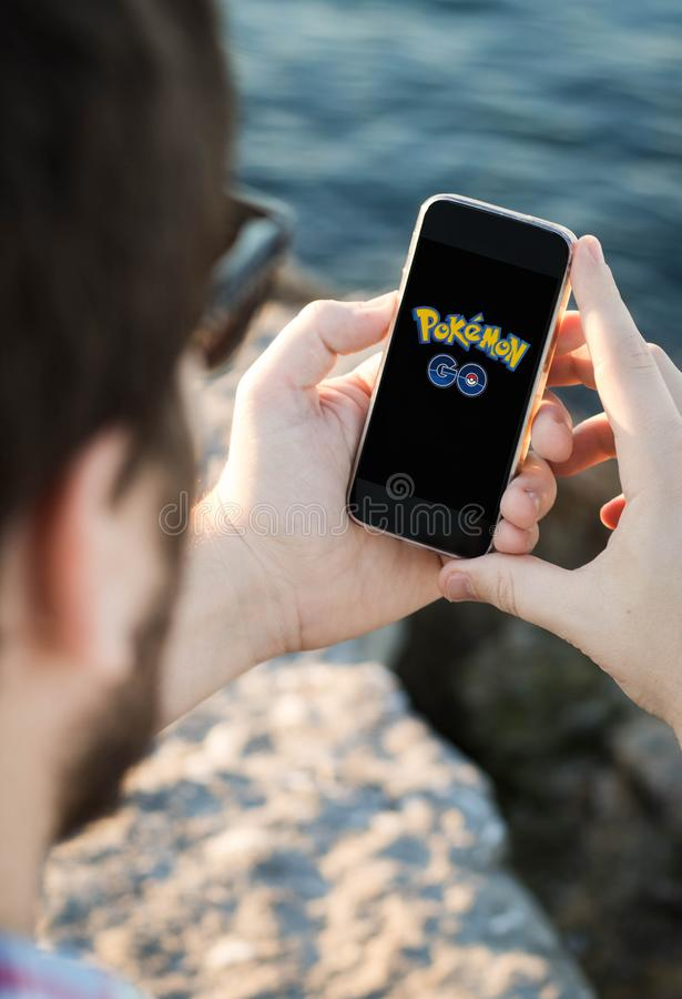 Man with sunglasses using the smartphone near the sea with pokemon go logo royalty free stock photos