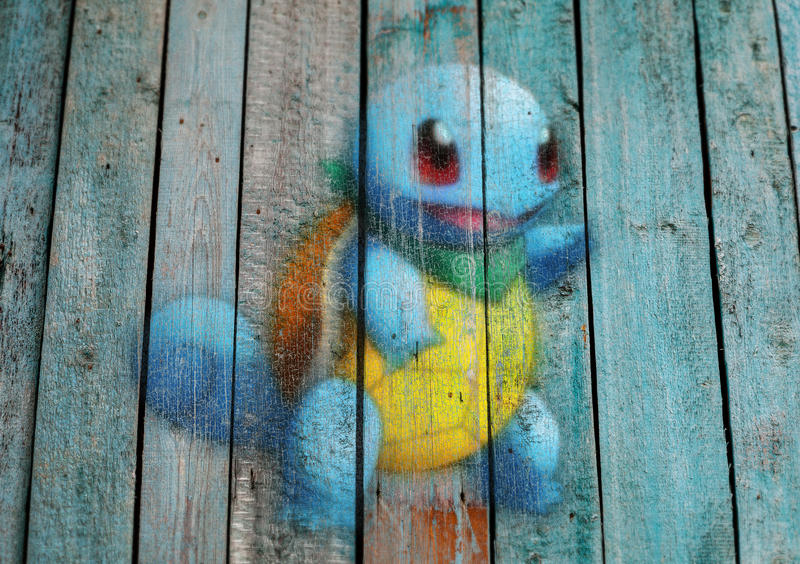 Pokemon GO monster drawn on wood background. Pokemon Go, the new augmented reality game that lets you walk in the real world to catch the monsters. A monster is royalty free stock photos