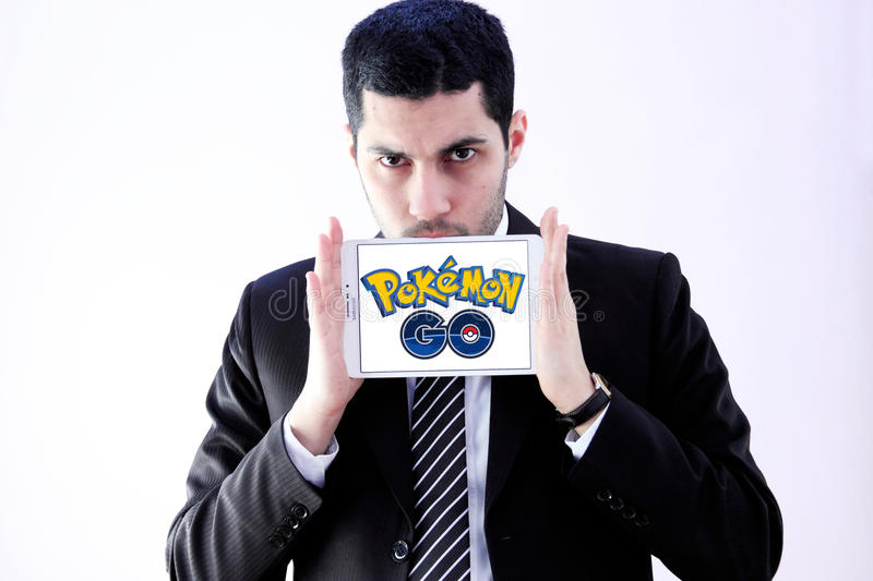 Pokemon go. Most famous smartphone game pokemon go logo on white tablet holded by arab muslim businessman. this game is travel between the real world and the stock photo