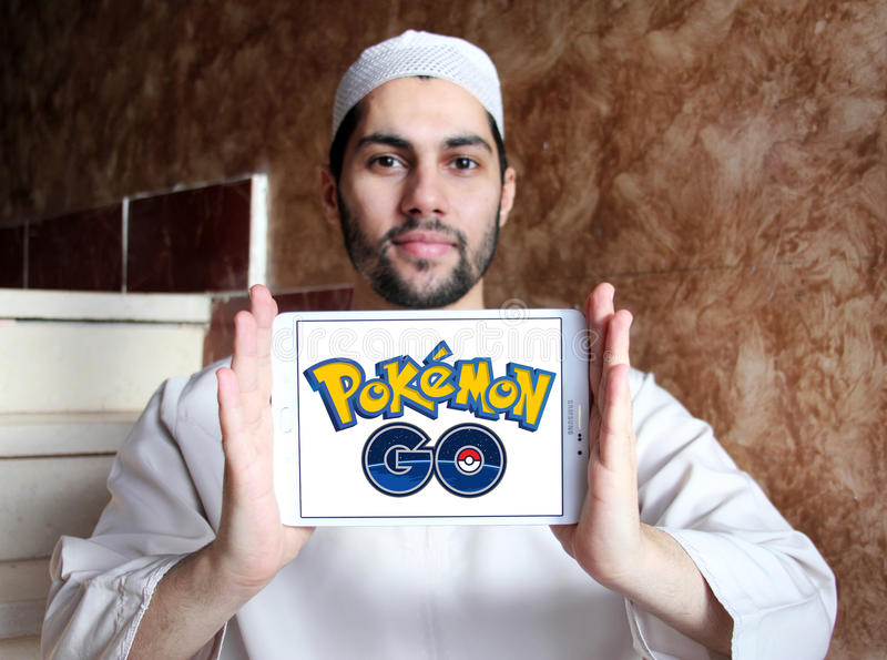 Pokemon go. Most famous smartphone game pokemon go logo on white tablet holded by arab muslim man .this game is travel between the real world and the virtual stock image