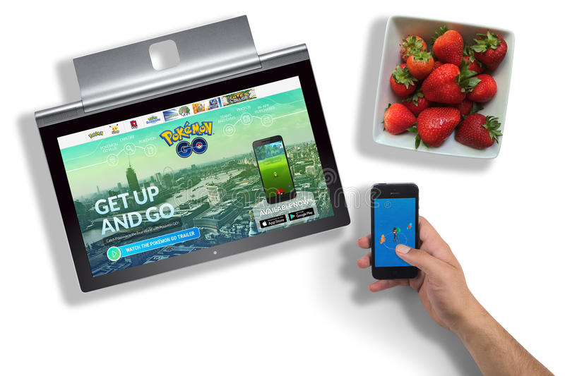 Pokemon Go website on laptop screen and app on hand held phone stock images