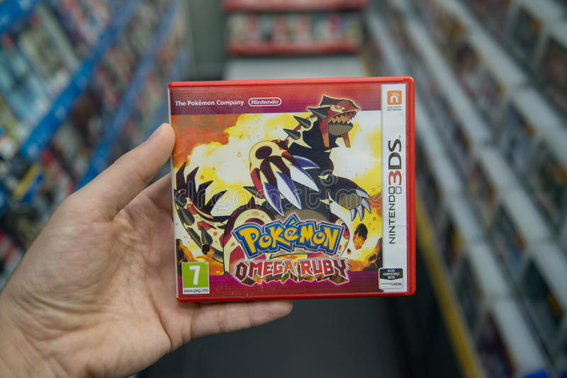 Pokemon Omega Ruby videogame. Bratislava, Slovakia, circa april 2017: Man holding Pokemon Omega Ruby videogame on Nintendo 3DS console in store stock photography