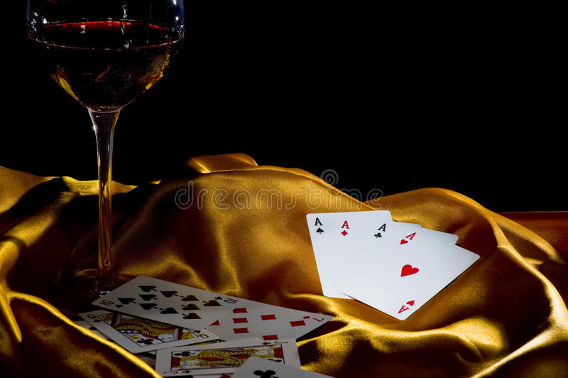 Poker ace and wine. Poker ace and a glass of wine on a golden silk. low key shot with focus on the 4 A stock photos