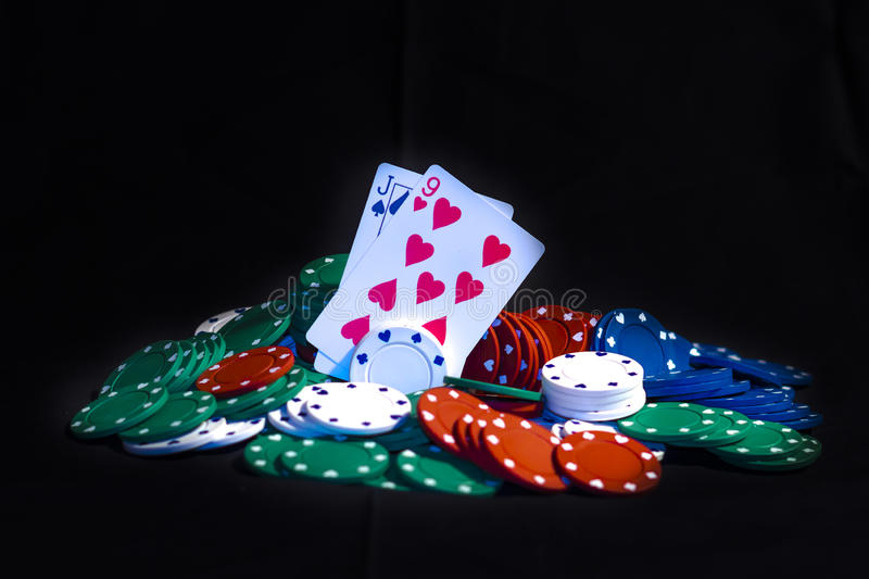 Poker cards and Casino chips isolated. Casino chips, playing cards isolated on black background royalty free stock images