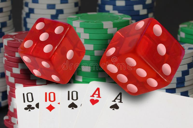 Poker cards showing full house and chips, jetons and red dices royalty free stock image