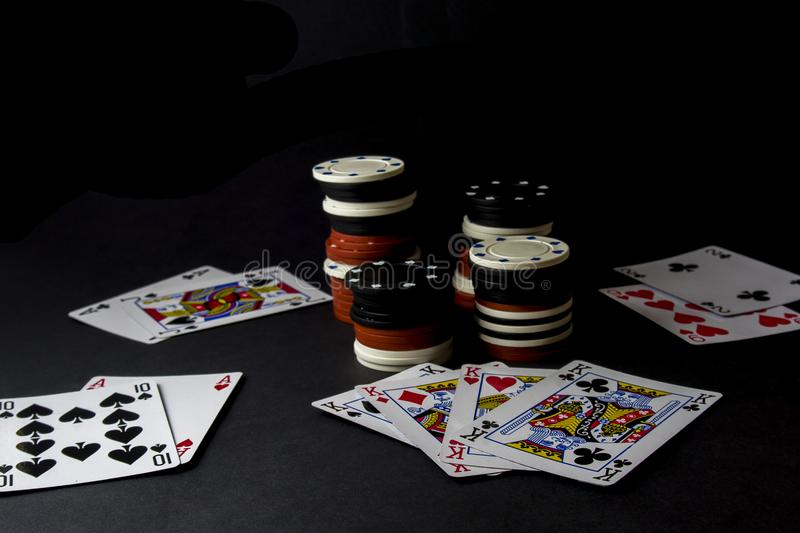 Poker cards and stacks, lot of chips over black. All in, four of stock photos