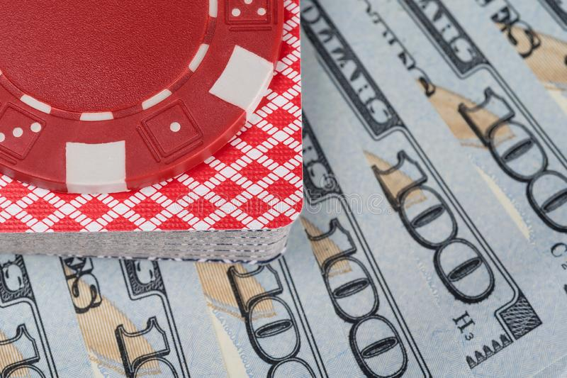 Poker chip lying on a deck of playing cards against the background of hundred dollar bills close up royalty free stock images