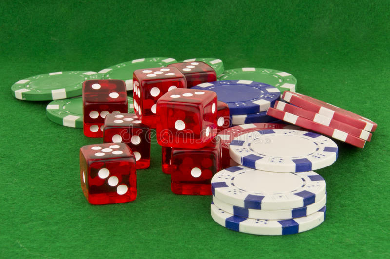 Poker chips and dice on green. Green beize with poker chips and dice royalty free stock photos