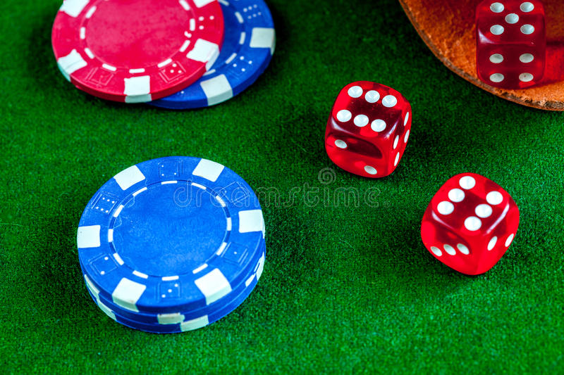 Poker chips and dice on green background top view.  stock photos