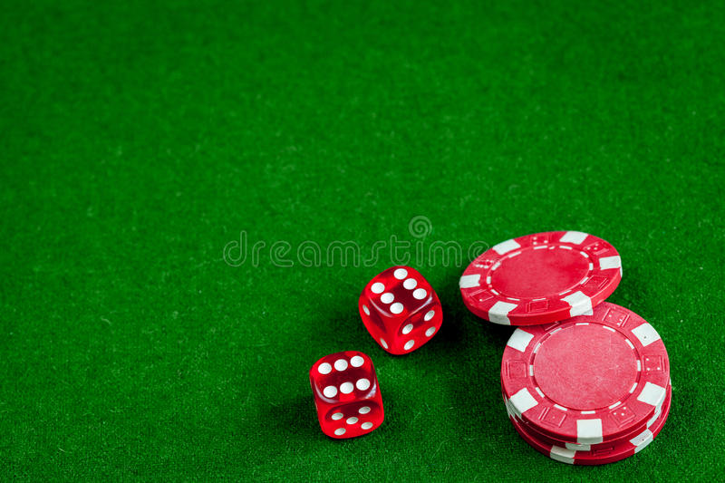 Poker chips and dice on green background top view.  royalty free stock image