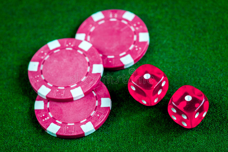 Poker chips and dice on green background top view.  royalty free stock photo