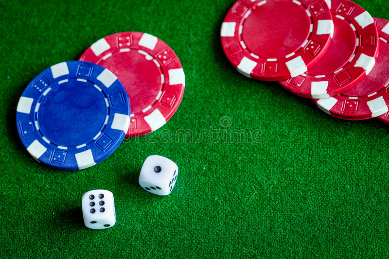 Poker chips and dice on green background top view.  royalty free stock photography