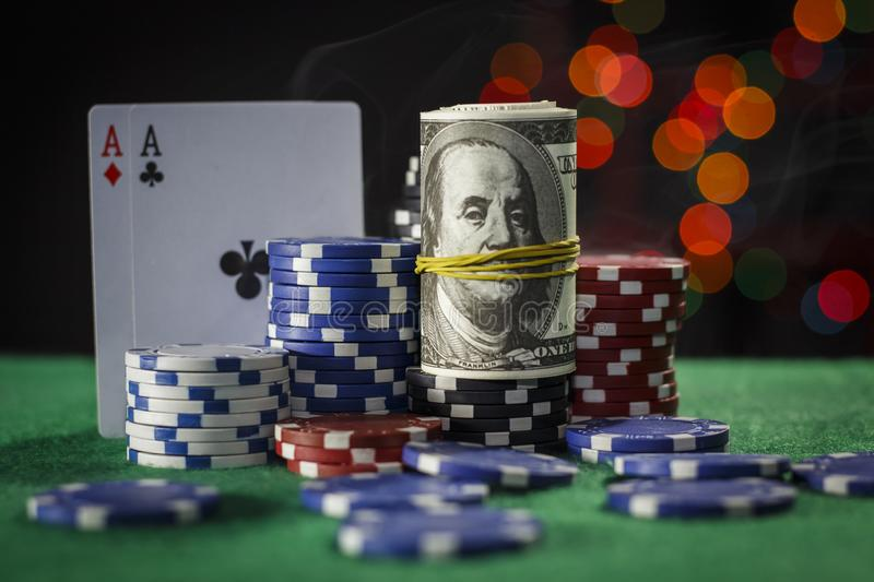 Poker chips, dollars and a pair of aces royalty free stock photo