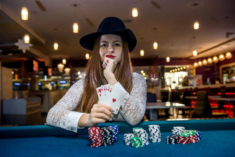 Poker chips and female hands holding playing cards.  royalty free stock photo