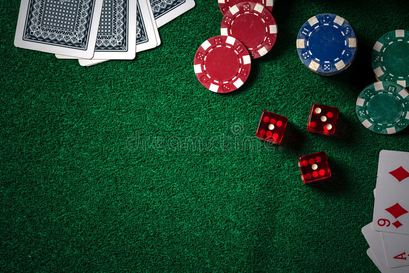 Poker chips and gamble cards on casino green table with low key stock photo