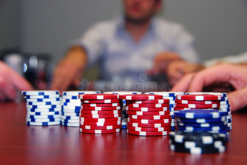 Poker Chips with Players in Background stock photo