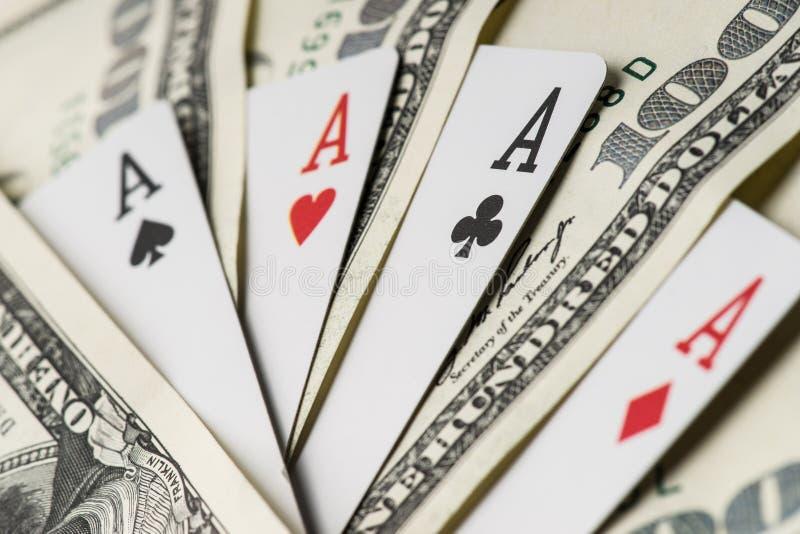 Poker för fyra överdängare som spelar kort bland U S Dollar royaltyfri foto