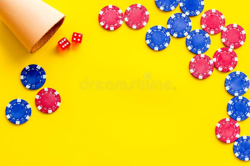 Poker frame. Chips and dices on yellow background top-down copy space stock images