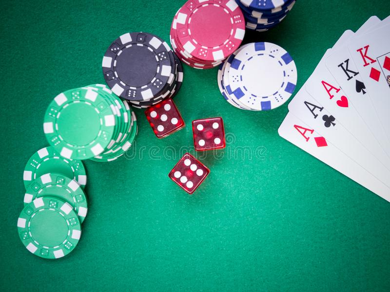 Poker full house of aces and kings on green table with red cubes and poker chips royalty free stock photos