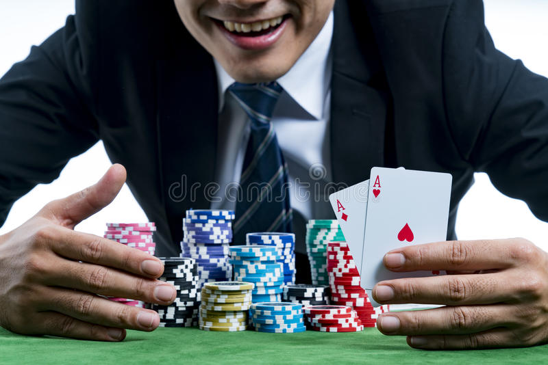 The poker gambler is showing a pair of aces and smiling hold bet stock photography