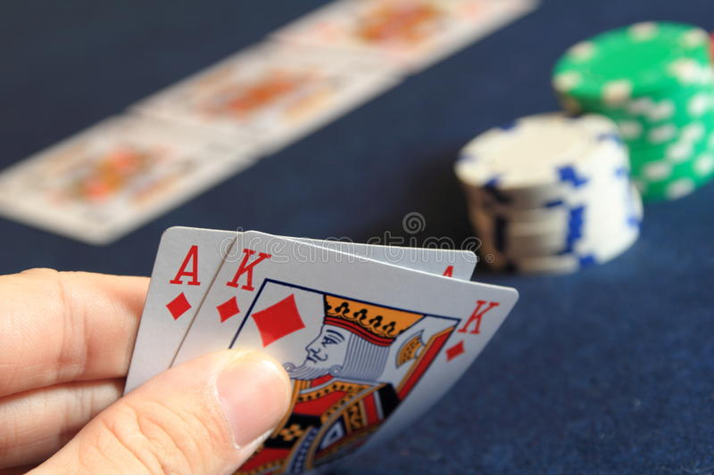 Poker hand. Poker player holding his cards in hand royalty free stock photo
