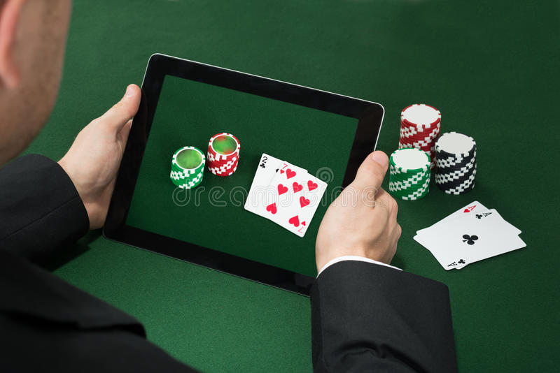 Poker Hand With Digital Tablet Showing Chips And Cards royalty free stock photography