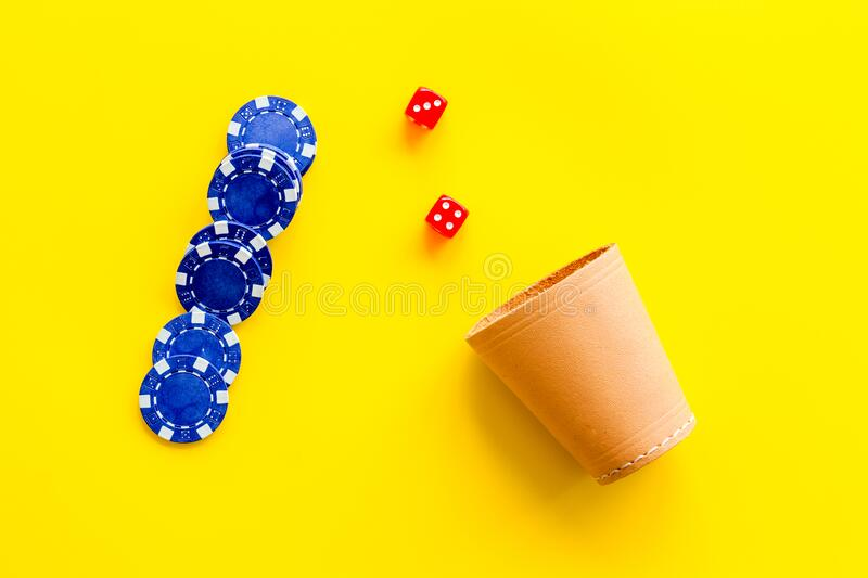 Poker hazard game concept. Chips, dices, cup for dice on yellow background top-down royalty free stock image