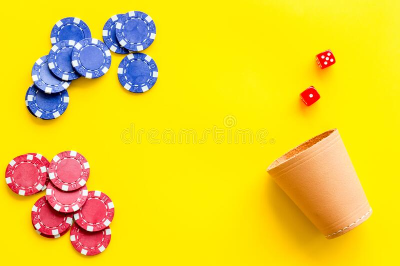 Poker hazard game concept. Chips, dices, cup for dice on yellow background top-down copy space royalty free stock images
