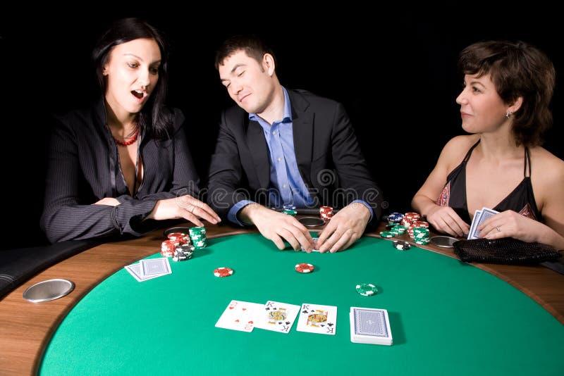 Poker night. Friends playing poker in the casino at night stock photo