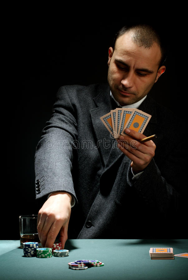 Poker player. Portrait of a poker player over black background stock image