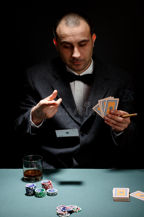 Poker player. Portrait of a poker player over black background royalty free stock images